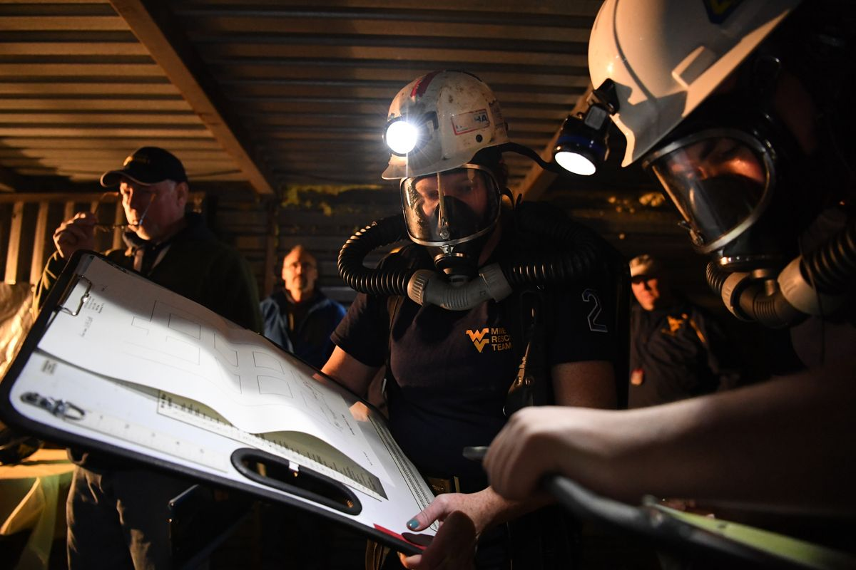 Miners underground looking at something with a light