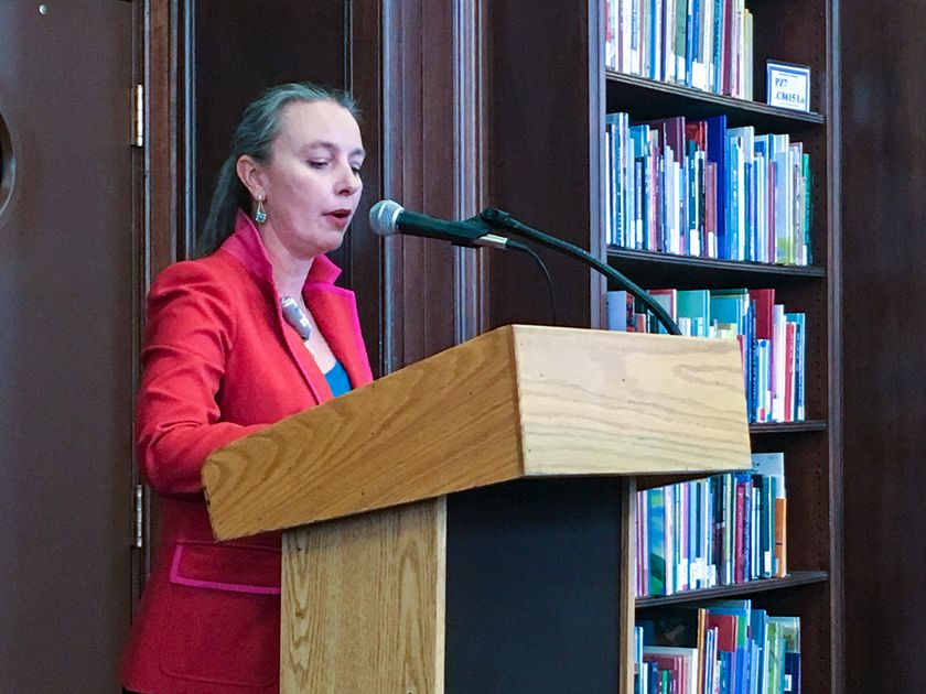 woman stands in red jacket speaking at microphone/podium with books in the background