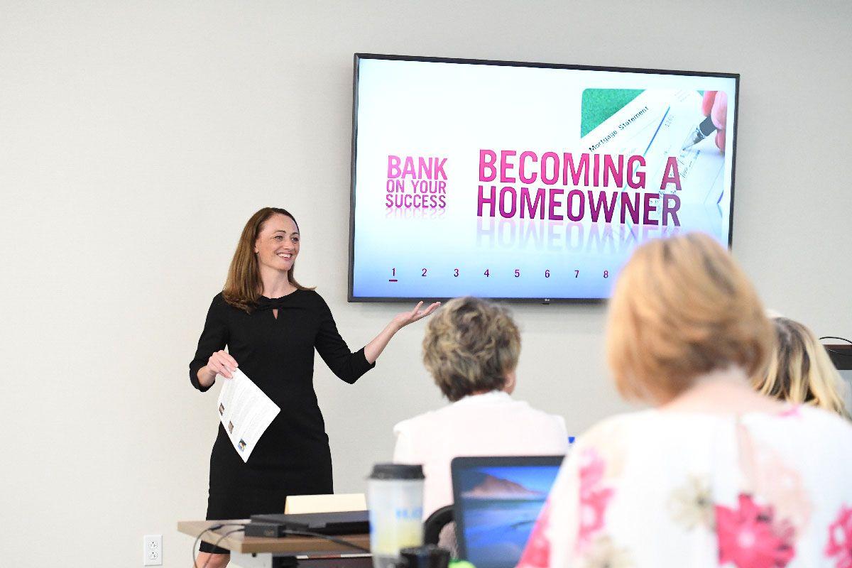 Woman in a black dress teaching class.