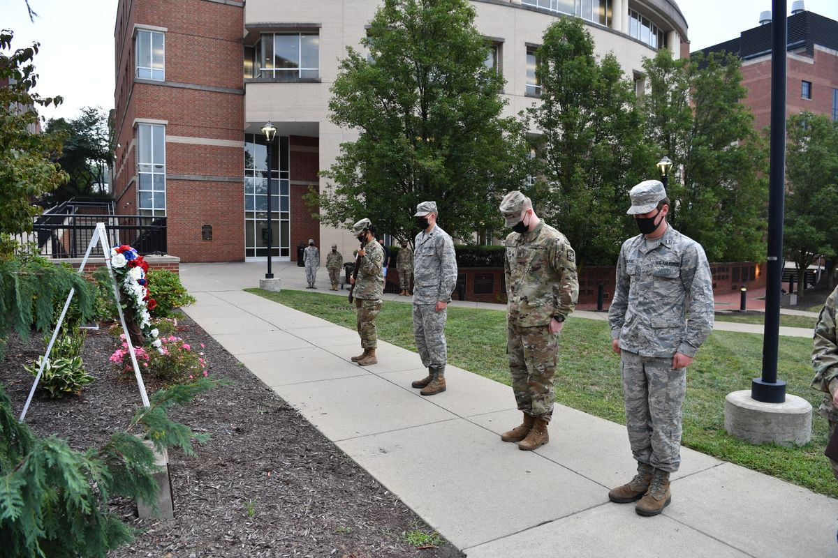 ROTC Cadets stand in uniform, in front of a wreath