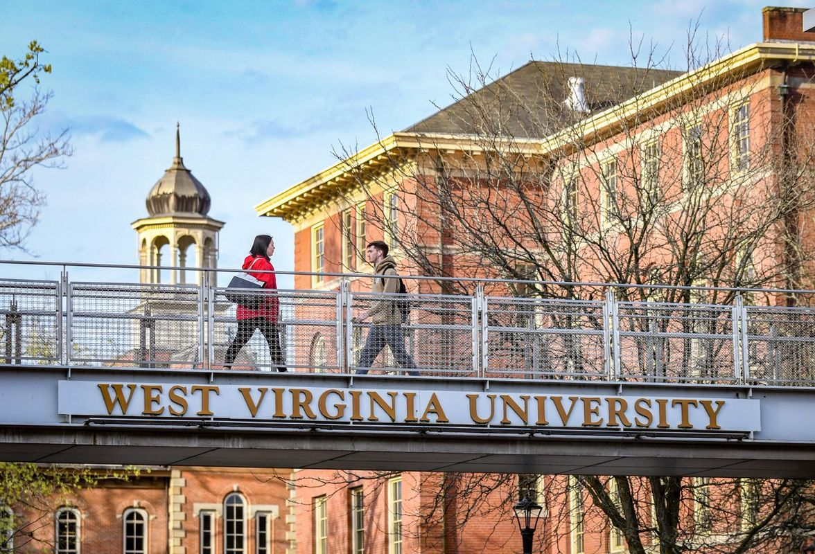 people walk across a footbridge with West Virginia University on the beam