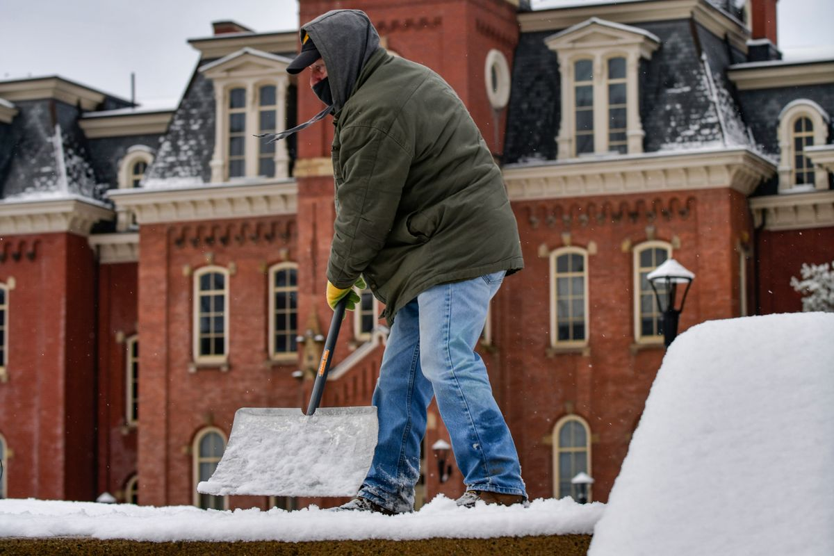man shovels snowy steps