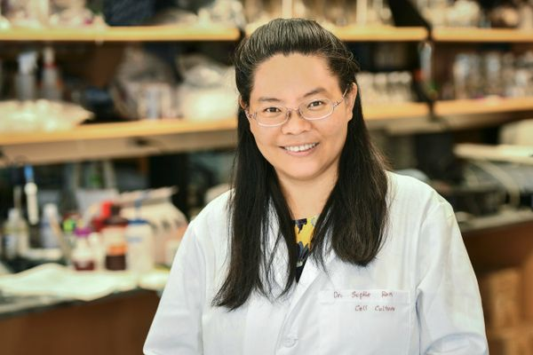 Smiling Asian woman in lab, wearing lab coat