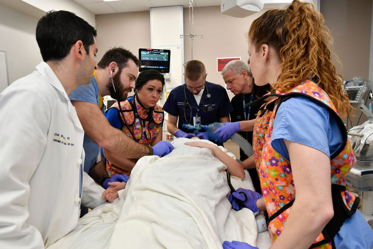 a group of medical professional gather around a patient in a hospital