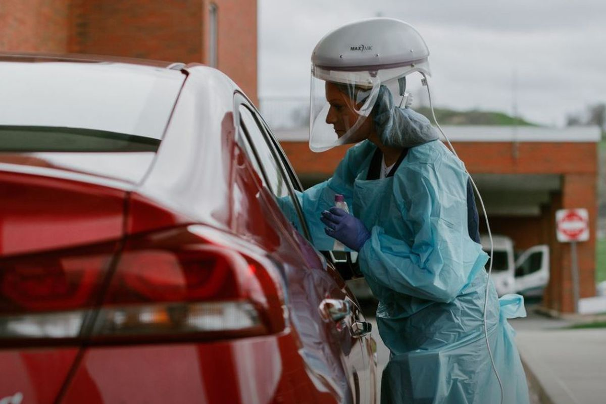 Woman in green medical protective gear administers COVID-19 test to a patient in a red car