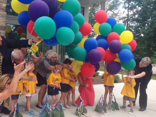 Students stand in yellow shirts with multi-color balloons