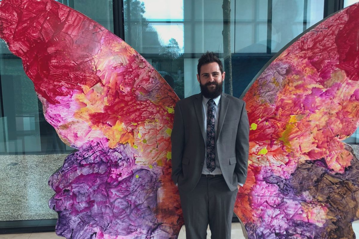 man stands in front of colorful insect wings sculpture