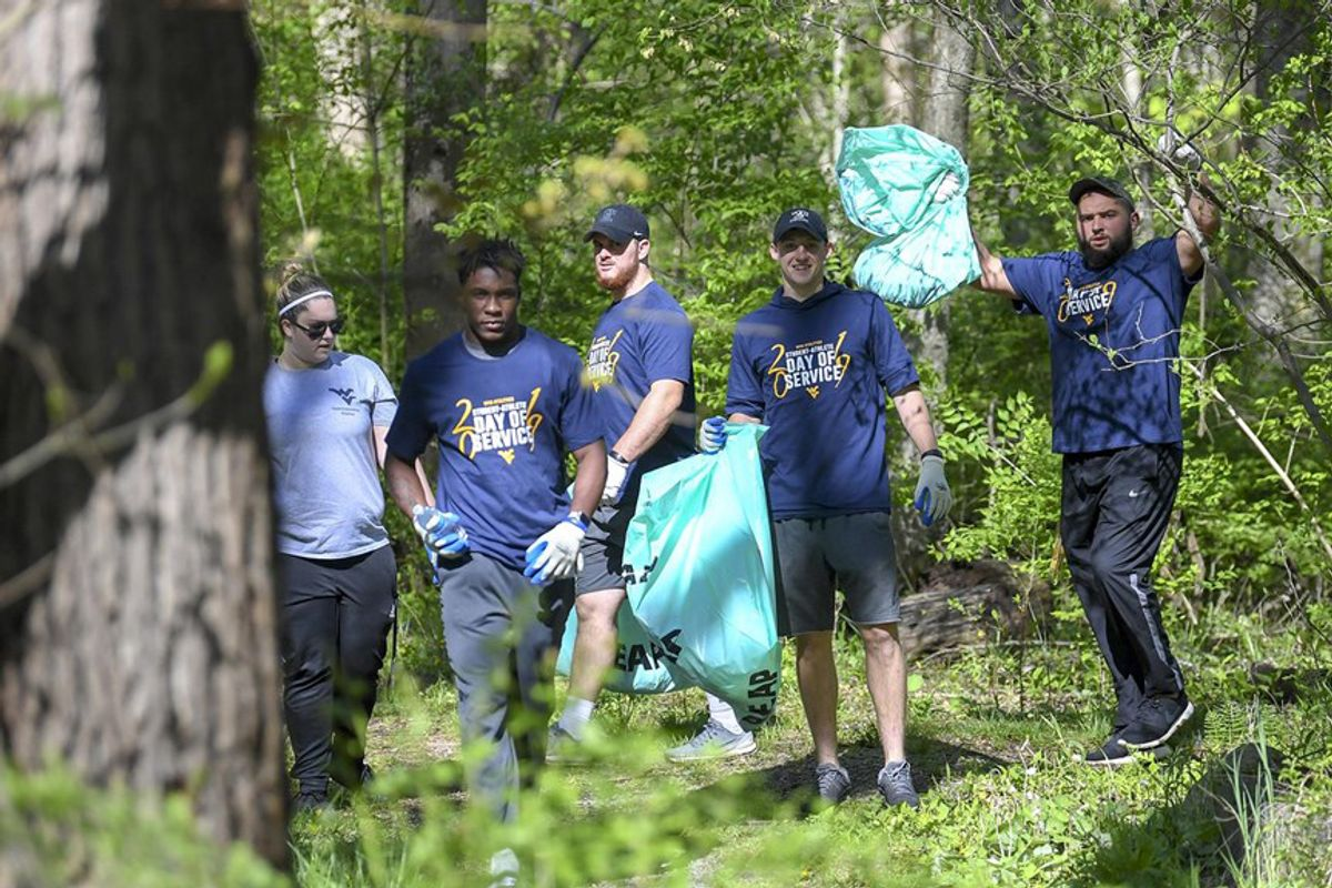 men and women pick up trash in a forest