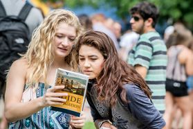 New students look through the Guide to Graduation as they attend the Eberly College academic session on the Life Sciences Green during Welcome Week 2016.