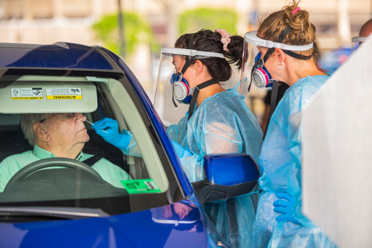 two people in medical protective gear test man in car