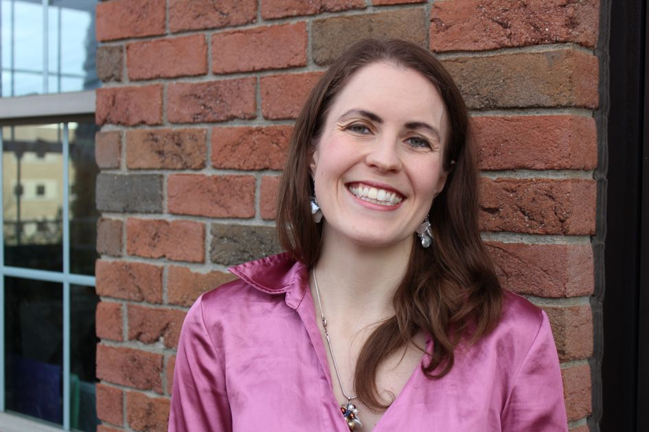 A smiling woman in a magenta blouse stands in front of a brick wall