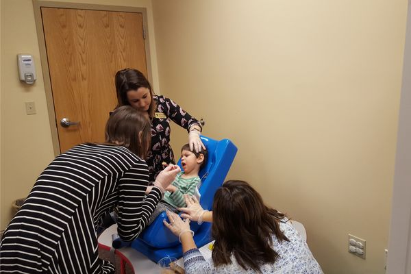 Speech pathology LEND trainee, Emily Corley, introduces spoon feeding to client as Cassie Miller, Feeding Clinic mentor, advises on technique.