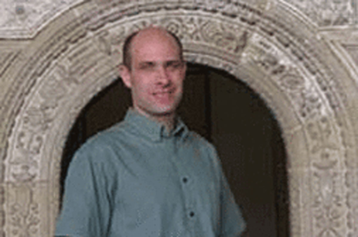 Smiling man in green shirt in front of archway
