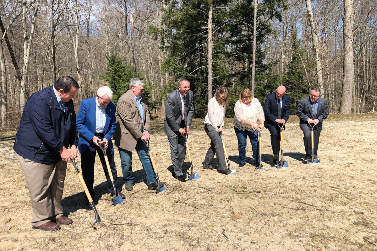 Seven people stand with shovels in the dirt to break ground in a field with trees in the background