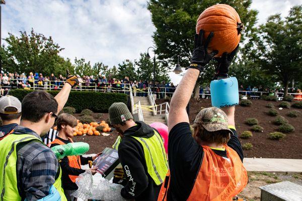 A man holds a pumpkin in the air