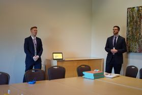 Two men in suits give a presentation in a meeting room