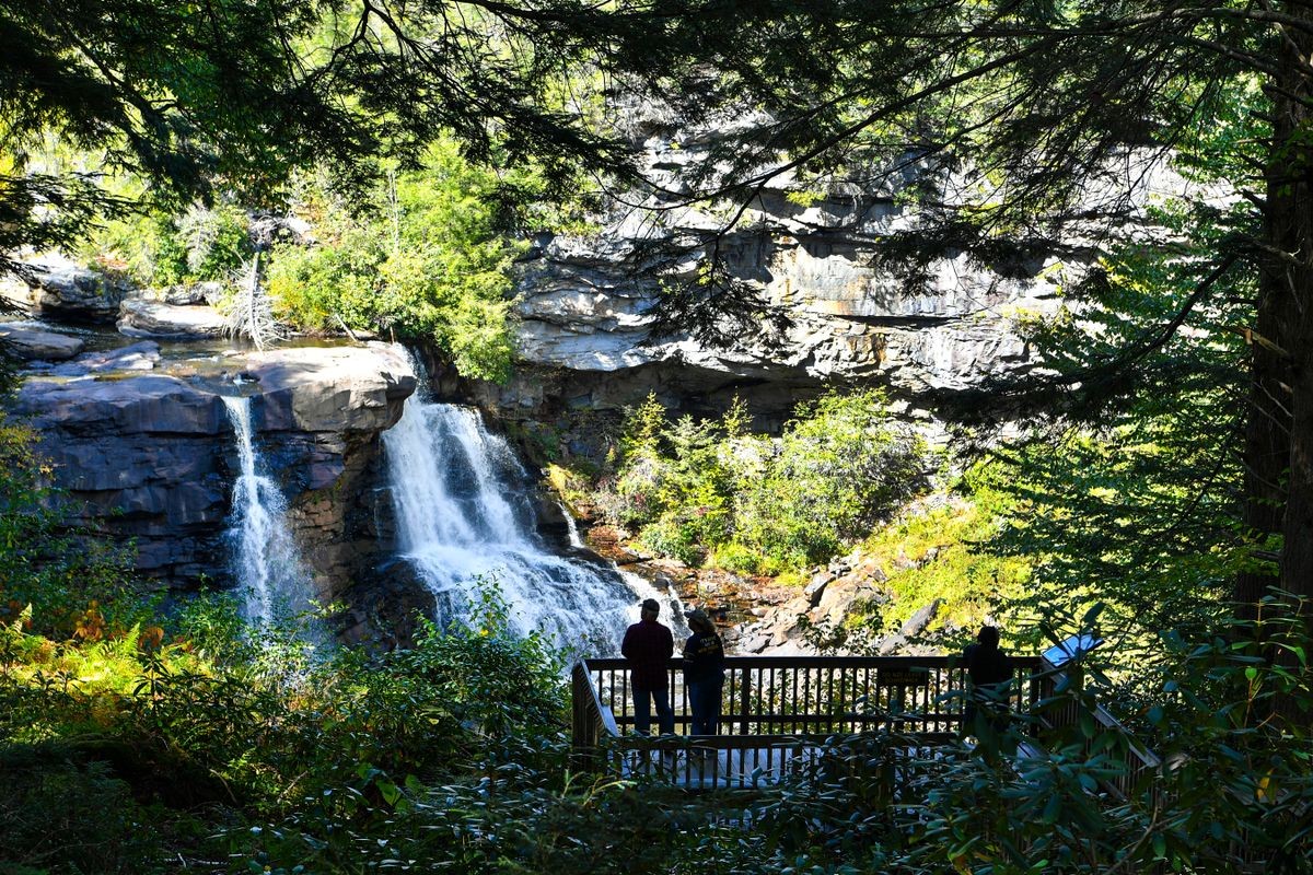people stand in shadows at a waterfall