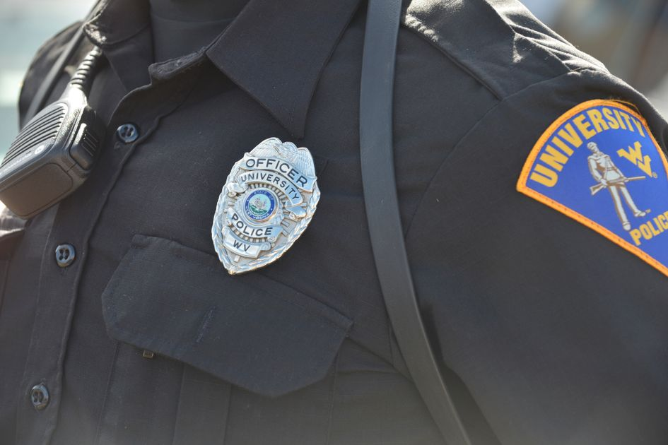 Police officer stands in black uniform with University Police logo and badge
