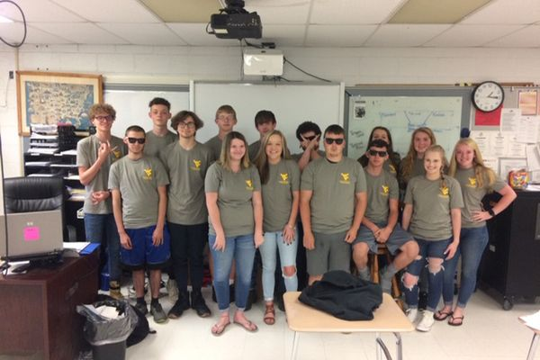 A group of 15 students in matching grey WV t shirts posing in a classroom for a photo.