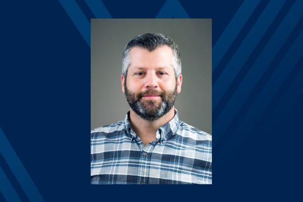 man in plaid shirt, dark hair, graying beard