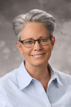 smiling woman with grey hair and glasses