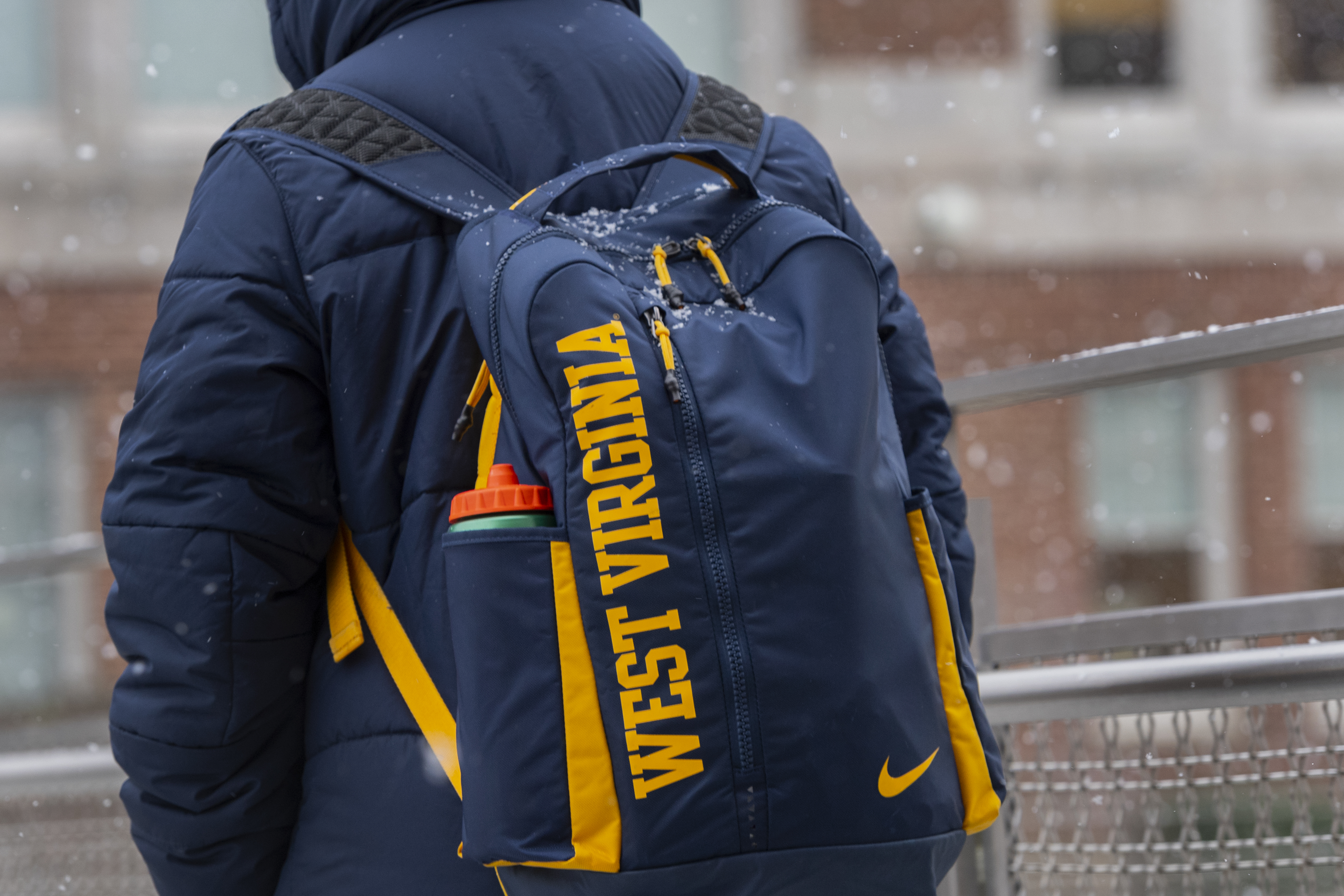 WVU student wears a backpack on the way to class in the snow.