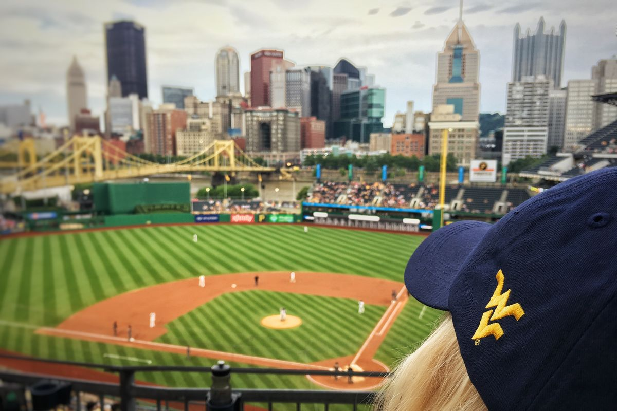 Photo of a baseball diamond with a city-scape in the background, dark blue hat with flying WV in the foreground