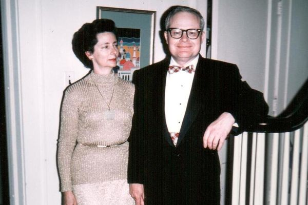 Woman wearing beige sweater with gold belt and a man wearing a black suit and white button-up shirt with bow tie