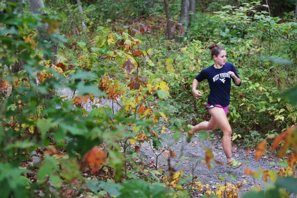 woman running on trail in woods