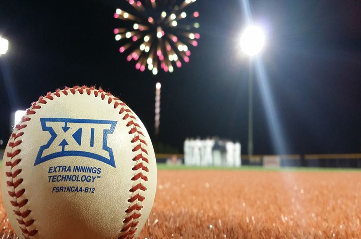 Baseball sitting on field with fireworks in the background, in the distance, out of focus.
