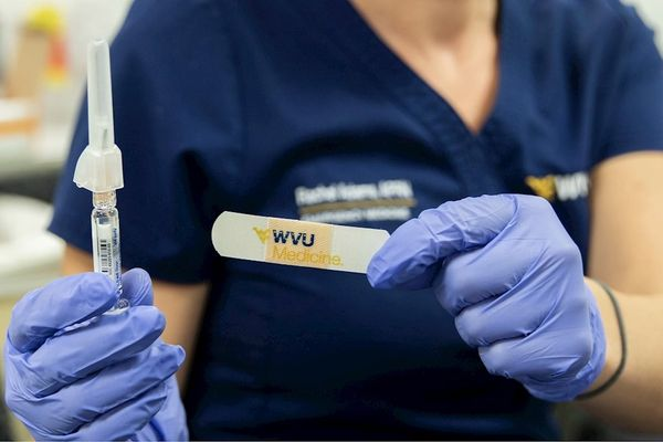 nurse in WVU Medicine scrubs holding up syringe and bandage