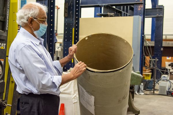 older Indian man holding trash can with mask on