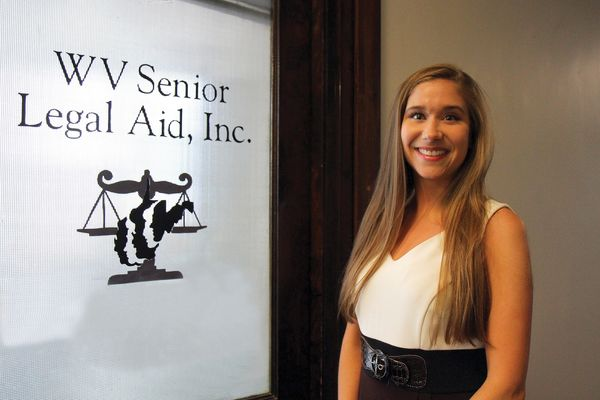 Law student standing in front of door with WV Senior Legal Aid, Inc. on it.