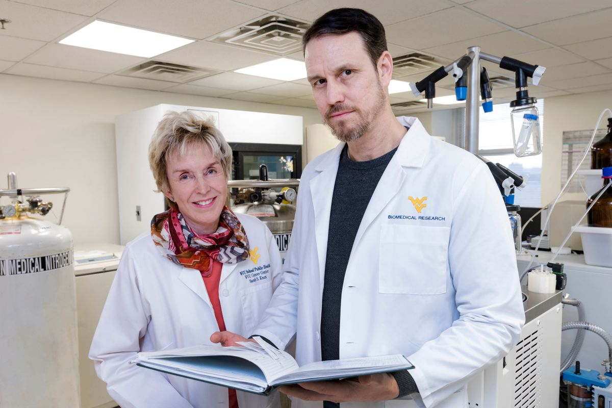 Two WVU doctors looking through papers