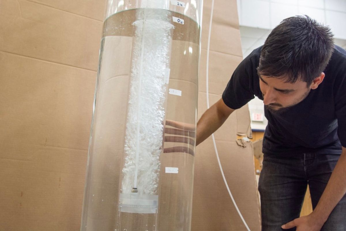 Man standing next to a glass tube.