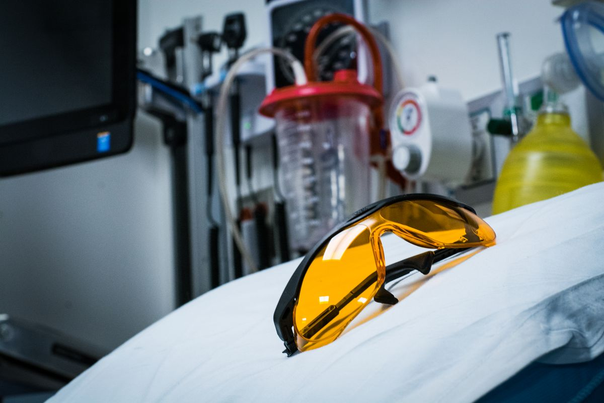 A pair of orange-colored glasses rests on a white surface with medical equipment in the background