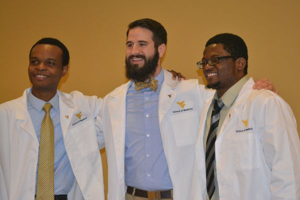 Three male students stand together after they receive their white coats