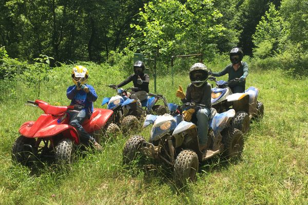 Four riders wearing helmets sit atop all-terrain vehicles in a grassy field