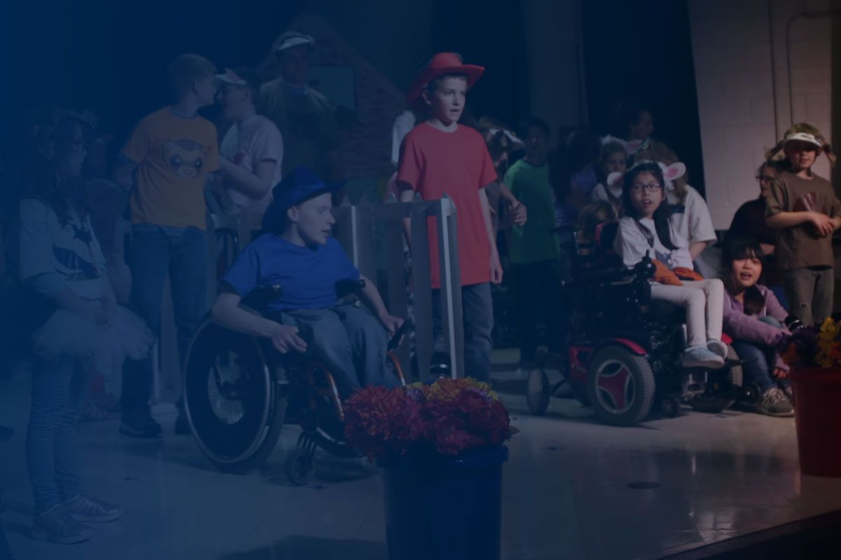 Dim photo of children in wheelchairs and with crutches