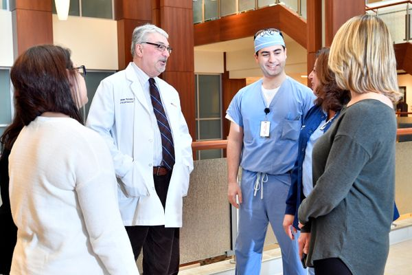 WVU School of Medicine resident Habib Zalzal (third from right) talks with Hassan Ramadan, chair of WVU's Department of Otolaryngology, Head and Neck Surgery (fourth from right), and other members of his research team