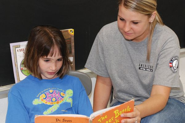 AmeriCorps volunteer reads with an Energy Express student