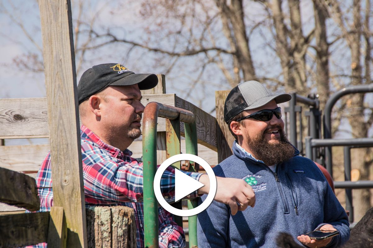 two men stand at a fence