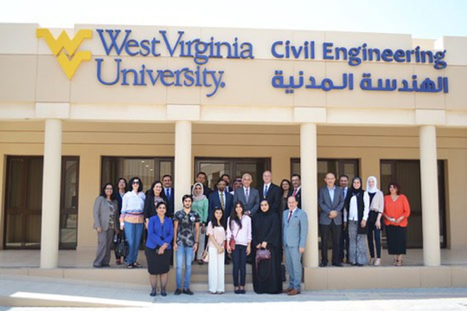 Large group of people standing on a porch; flying WV West Virginia University Civil Engineering above on the building