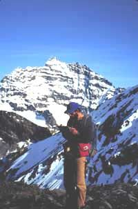 Man with a clipboard in front of snow-covered high peaks