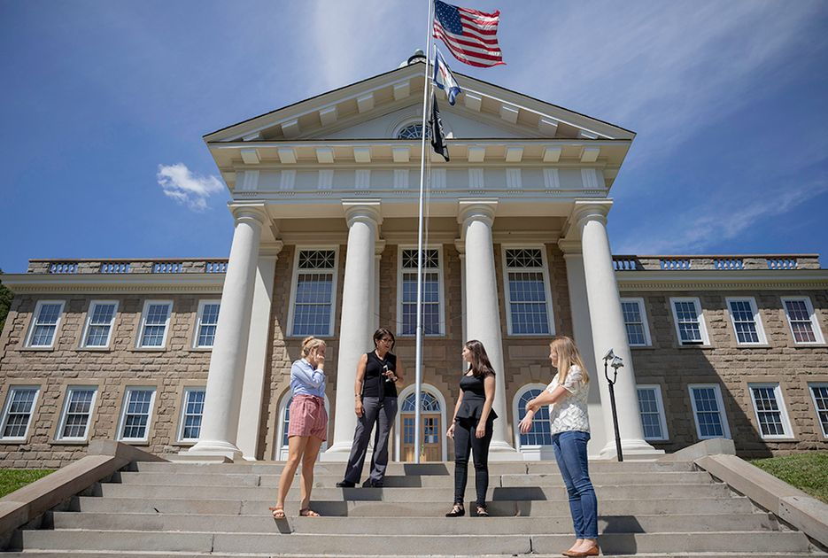 Four women stand on the steps of a courthouse