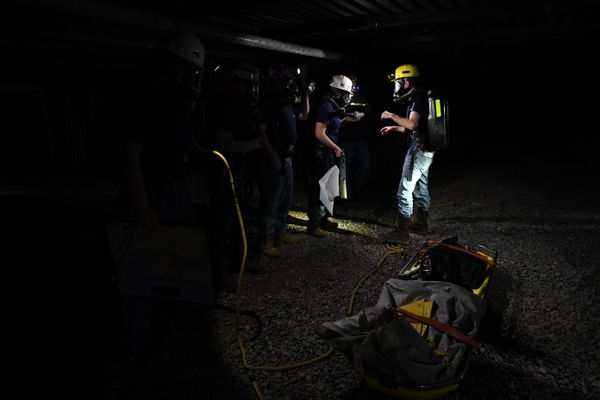 men wearing hard hats and head lamps work in a dark space