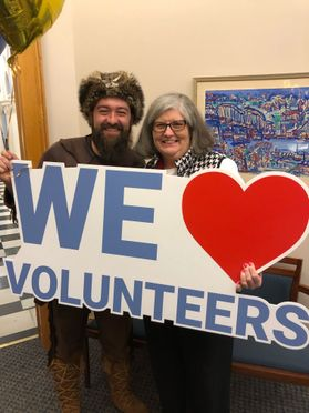 WVU Mountaineer with woman and sign that says WE love Volunteers