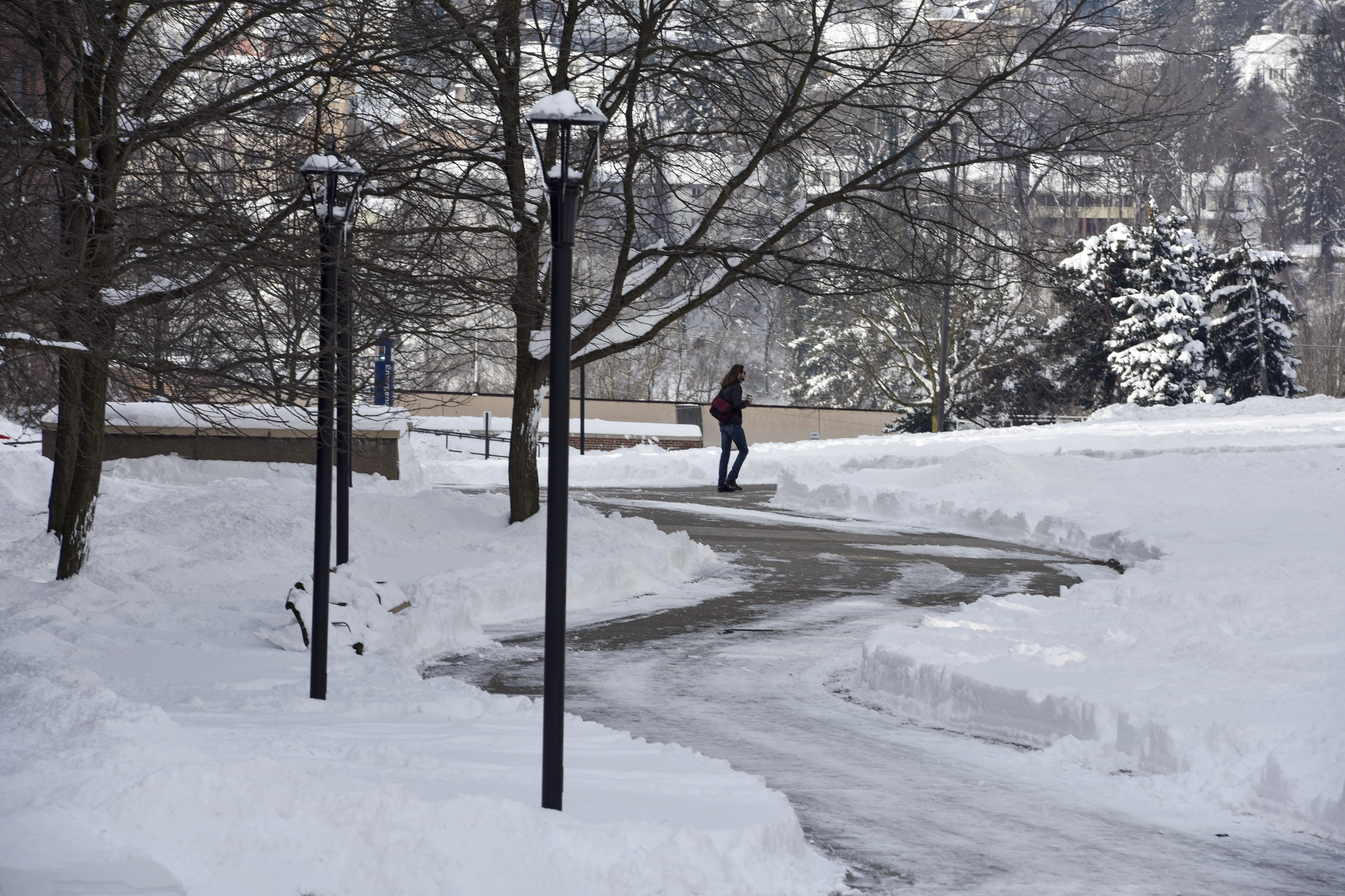 Student walks on snow covered path on WVU's downtown campus.