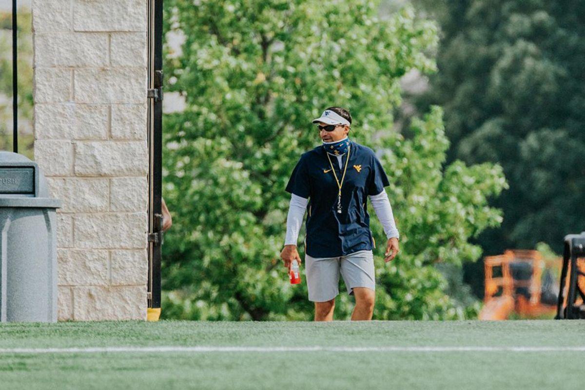man in shorts, polo, visor, sunglasses walks on grass