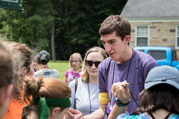 Young man in purple shirt talks to a group of people